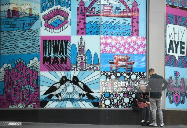 People sit and stand near artwork in Newcastle city centre, north-east England, on September 17, 2020. - The British government on Thursday announced...