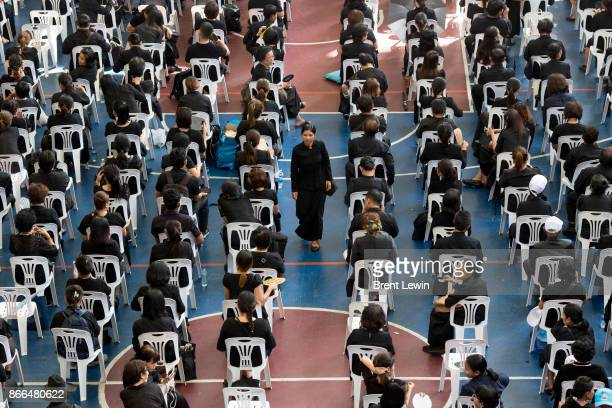People sit and wait for access to the funeral of late Thai King Bhumibol Adulyadej on October 26 2017 in Bangkok Thailand Tens of thousands of people...