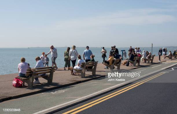 People sit and walk along the promenade in the sun by Westcliff beach on March 30, 2021 in Southend, United Kingdom. Despite todays temperature...