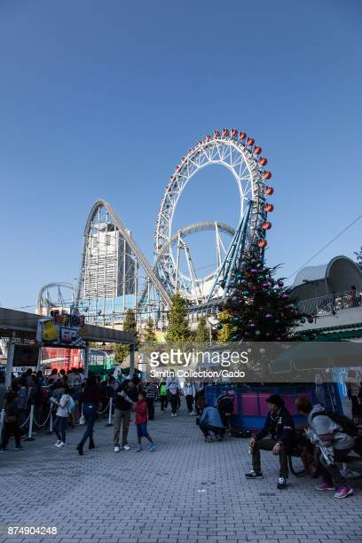 People sit and walk in a large crowd at Tokyo Dome City an entertainment area in Bunkyo ward Tokyo Japan November 3 2017