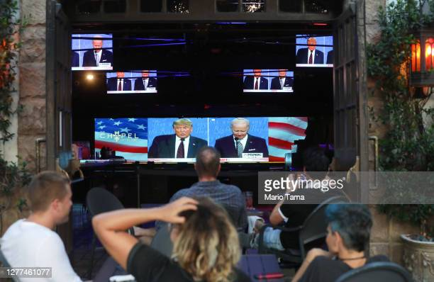 People sit and watch a broadcast of the first debate between President Donald Trump and Democratic presidential nominee Joe Biden with socially...