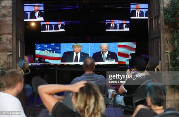 People sit and watch a broadcast of the first debate between President Donald Trump and Democratic presidential nominee Joe Biden at The Abbey, with...