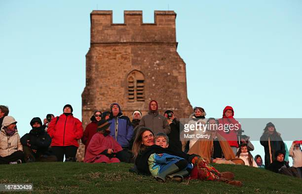 People sit and watch the sun rise as they join in a Beltane dawn celebration service in front of St Michael's Tower on Glastonbury Tor on May 1 2013...