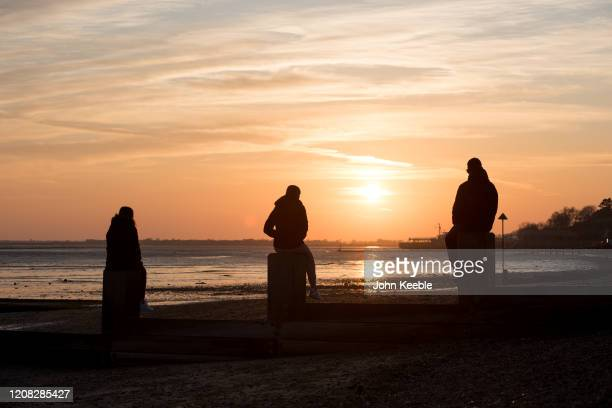 People sit and watch the sunset from the beach on March 26 2020 in Chalkwell England British Prime Minister Boris Johnson announced strict lockdown...
