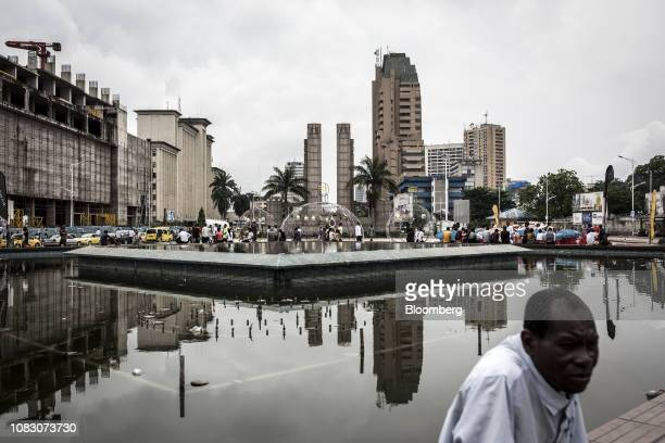 People sit around a disused fountain in the business district of Kinshasa Democratic Republic of the Congo on Friday Jan 11 2019 The disputed...