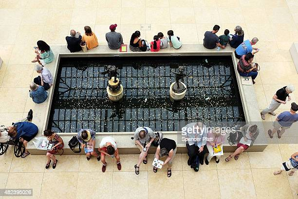 People sit around a fountain at the Metropolitan Museum of Art on July 30 2015 in New York City The Met recently announced that it drew 63 million...