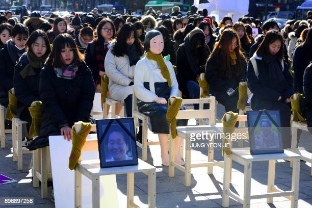 TOPSHOT People sit around a statue of a comfort woman during an installation of empty chairs during a performance event commemorating the death of...