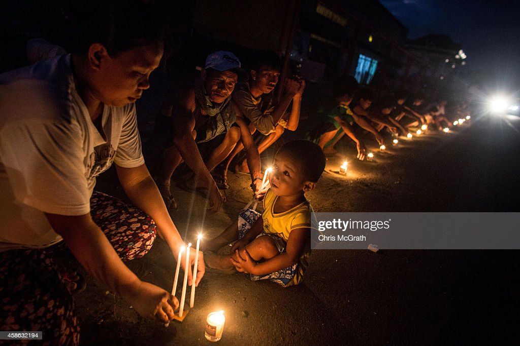TACLOBAN, LEYTE, PHILIPPINES - NOVEMBER 08: People sit around candles on the roadside in San Jose during the candlelight memorial on November 8, 2014 in Tacloban, Leyte, Philippines. People lined the roads with candles all across Tacloban from the airport to downtown in remembrance of the victims of Typhoon Haiyan. Residents and typhoon survivors from across the central Philippines attended memorial services, candlelight vigils and visited mass graves honouring those who lost their lives one year ago when Typhoon Haiyan, the strongest typhoon ever to make landfall swept across the region, leaving more than 6000 dead and many more homeless.