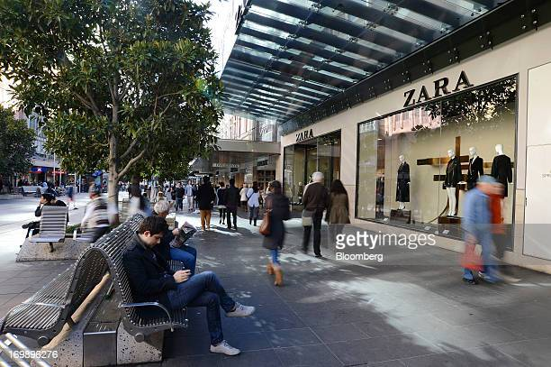 People sit as pedestrians walk past a Zara fashion store operated by Inditex SA on Bourke Street Mall in central Melbourne Australia on Sunday June 2...