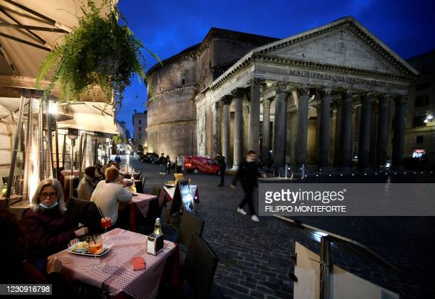 People sit at a bar terrace by the Pantheon in central Rome on February 1, 2021 amid an easing of restrictions against the spread of Covid-19...