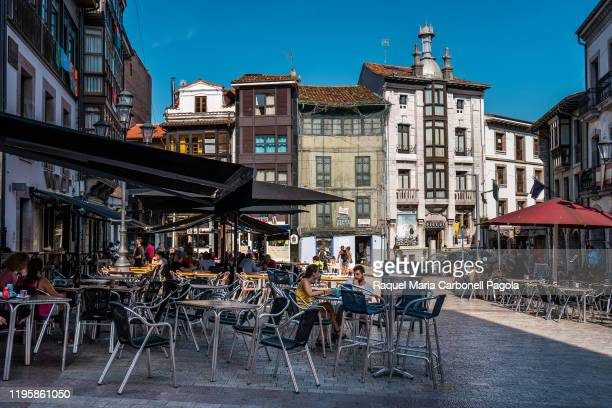 People sit at a bar terrace in a central square in a summer evening.