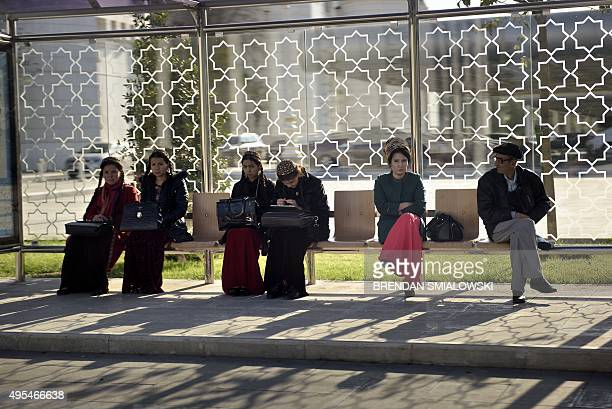 People sit at a bus stop while a motorcade with US Secretary of State John Kerry drives past on November 3 2015 in Ashgabat Kerry is traveling to...