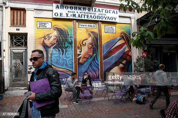 People sit at a cafe in front of a closed fabric store in Agia Irini square Athens Greece on Saturday April 25 2015 The downturn that decimated the...