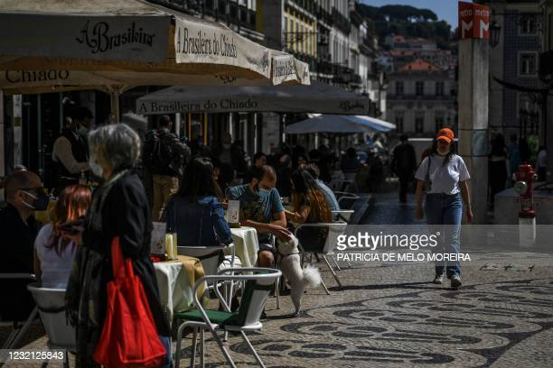 People sit at a cafe terrace in the Chiado district of Lisbon as the Portuguese government eased coronavirus restrictions on April 5, 2021. -...
