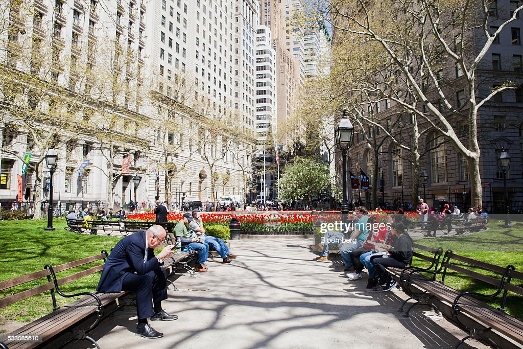 People sit at a park in the Financial District of New York, U.S., on Monday, April 18, 2016. U.S. stocks rose, with the S&P 500 bouncing from a seven-week low, led by a rally in technology shares amid ebbing anxiety over the potential for higher interest rates as early as next month. Photographer: David Williams/Bloomberg via Getty Images