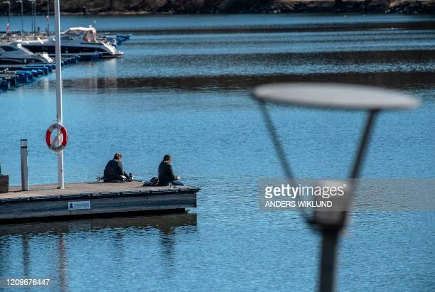 People sit at a quay in Stockholm, Sweden, on April 11, 2020 amid the new coronavirus COVID-19 pandemic. - Sweden has not imposed extraordinary...