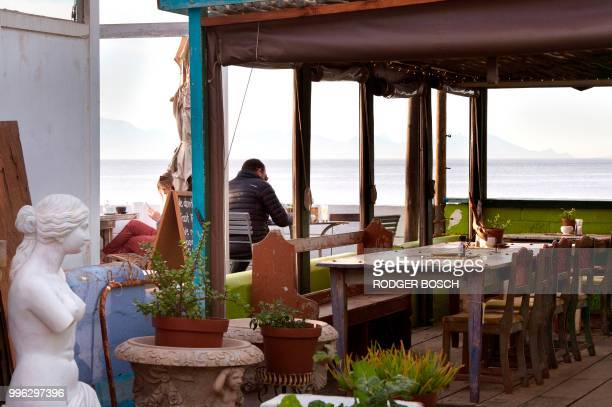 People sit at a restauarant in Kalk Bay a trendy fishing village about 30km from the city centre on July 11 in Cape Town Kalk Bay with a combination...