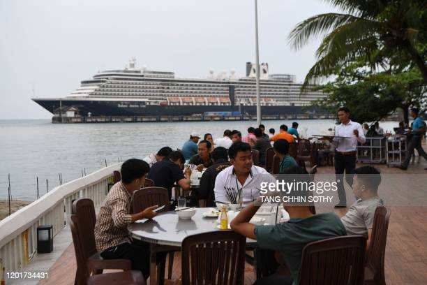People sit at a restaurant in front of the Westerdam cruise ship in Sihanoukville on February 19 2020 Cambodia's strongman premier has defended his...