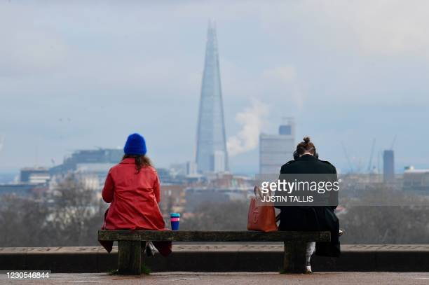 People sit at a social distance from one another on a bench on the top of Primrose Hill in London on January 12, 2021 with the Shard Tower in the...
