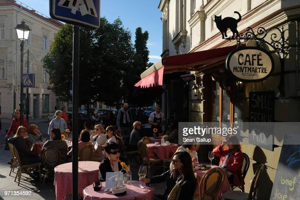 People sit at an outdoor cafe on June 6 2018 in Vilnius Lithuania Vilnius is the capital of Lithuania and a popular tourist destination