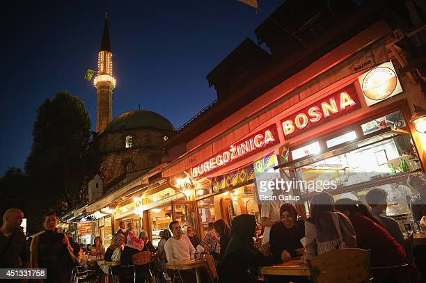 People sit at an outdoor restaurant specializing in burek near an illuminated mosque on the eve of the centenary of the assassination of Austrian...