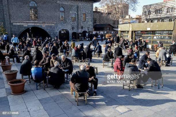 People sit at an outdoor tea house near Ulu Mosque in Diyarbakir's historic Sur district on January 11 2017 / AFP / ILYAS AKENGIN
