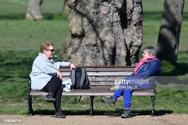 people sit at either end of a park bench as they talk in Clapham Common in south London on March 24 2020 after Britain's government ordered a...