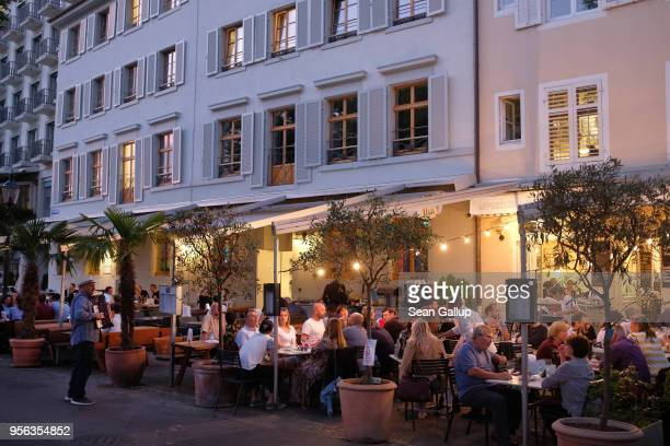 People sit at outdoor restaurants on the bank of the Rhine on May 7, 2018 in Basel, Switzerland. Basel, a quiet university town on the Rhine River in...