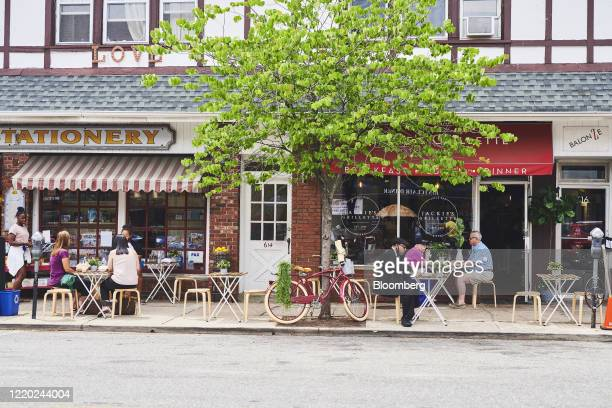 People sit at outdoor seating at a restaurant in Montclair, New Jersey, U.S., on Monday, June 15, 2020. New Jersey enters Phase 2 on Monday, opening...
