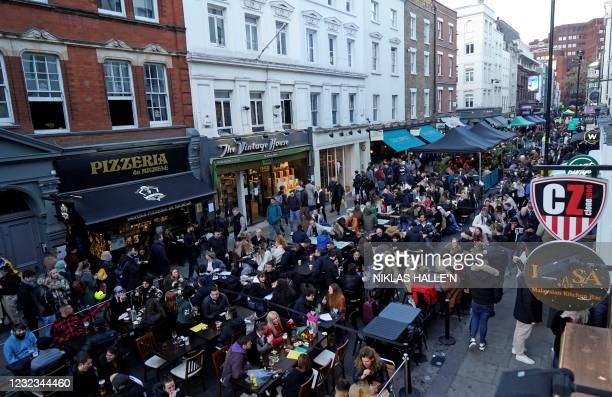 People sit at outside tables to eat and drink at re-opened bars and restaurants, in the street in the Soho area of London, on April 16, 2021...