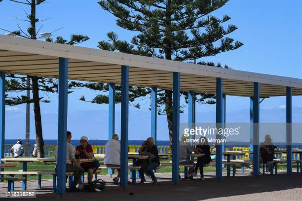 People sit at picnic tables despite warnings not to at Marourbra Beach on April 12, 2020 in Sydney, Australia. Australians have been urged to avoid...