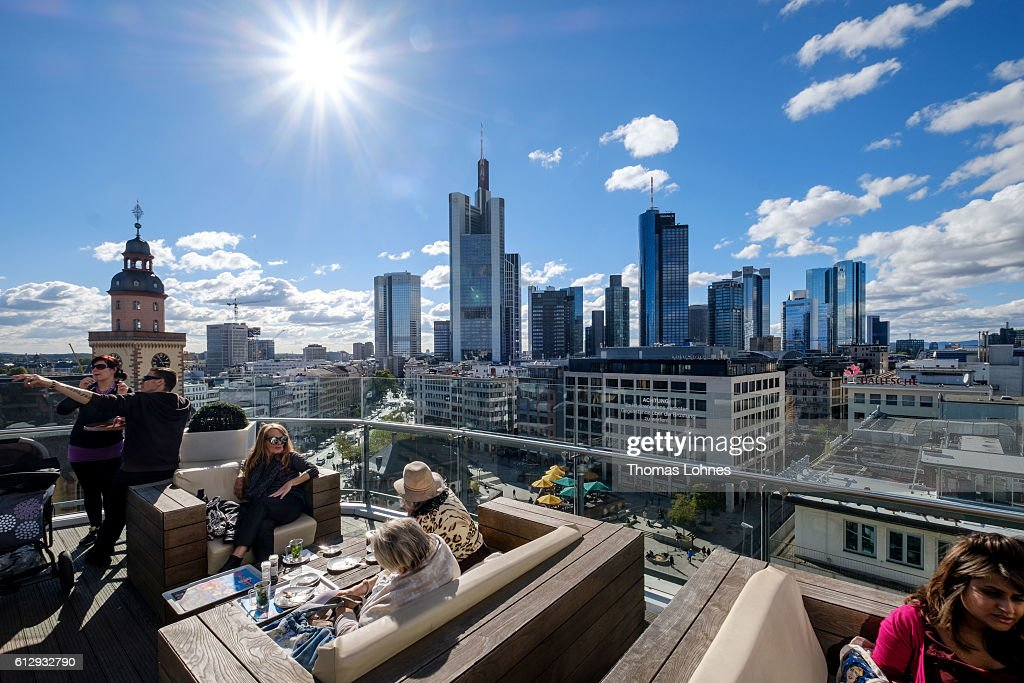 People sit at restaurant roof terrace with the skyline and finance district of Frankfurt on October 5, 2016 in Frankfurt, Germany. Banks across Europe are struggling as their profits have fallen amid an ongoing period of low interest rates, and many, including Commerzbank and Deutsche Bank of Germany, ING and ABN Amro of Holland, and Banco Popular of Spain, are responding by slashing thousands of jobs in an effort to cut costs.