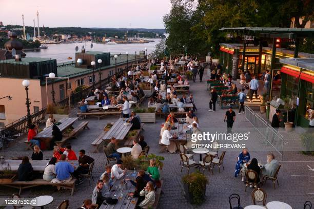 People sit at tables outside restaurants in Stockholm, after 10.30 pm as the Covid-19 restrictions for opening hours at restaurants and bars have...