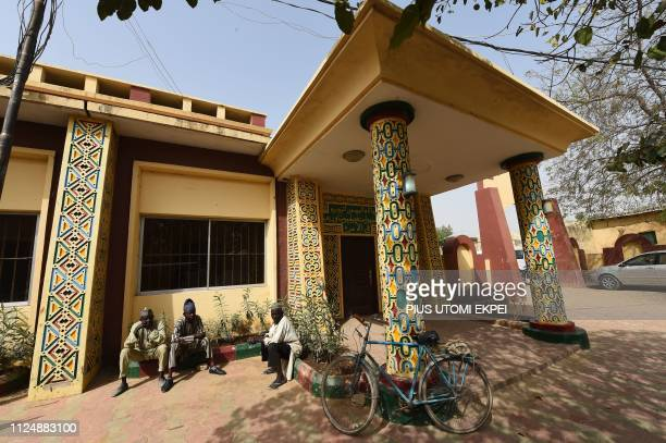 People sit at the gate to a hall in the Palace of the Emir of Kano Sanusi Lamido Sanusi in Kano on February 14 2019 The artistic framework projects...