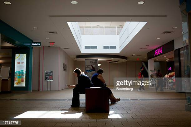 People sit at the Peter Pond Mall in Fort McMurray Alberta Canada on Tuesday Aug 13 2013 Canadian oil companies have benefited as the gap between...