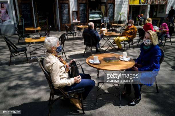 People sit at the terrace of a cafe in Bratislava on May 6 amid the novel coronavirus COVID-19 pandemic. - The Slovakian government is easing...
