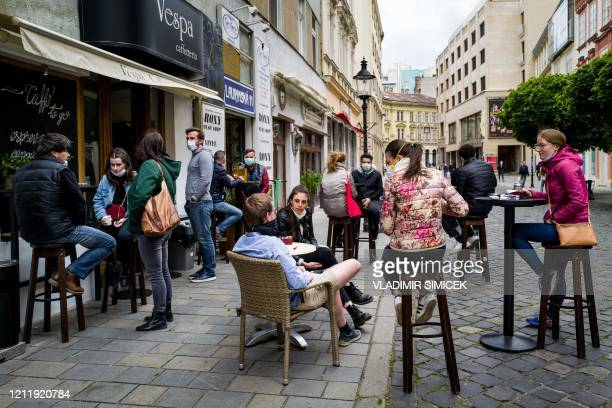 People sit at the terrace of a cafe in Bratislava on May 6 amid the novel coronavirus COVID19 pandemic The Slovakian government is easing...