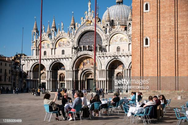 People sit at the terrasse of a cafe in front of the western facade of St Mark's Basilica on Piazza San Marco in Venice on May 20, 2021.