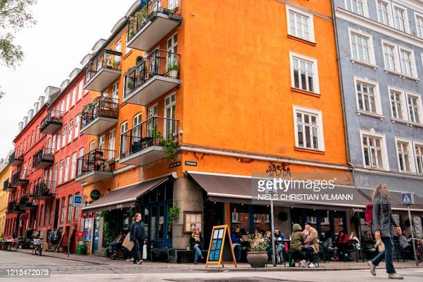 People sit at the terrasse of the Cafe Gavlen after it reopened in Copenhagen on May 18, 2020. - Restaurants, cafes and several other places opened...