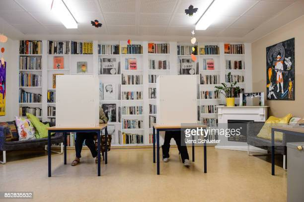 People sit behind voting booths as they fill in their election ballots at a polling station during German federal elections on September 24 2017 in...