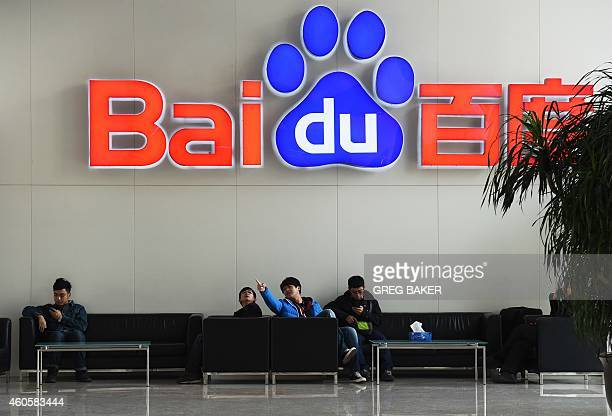 People sit below a Baidu logo at the Baidu headquarters in Beijing on December 17, 2014. Baidu, China's leading search engine, and ride sharing...