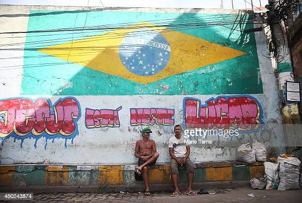 People sit beneath a Brazil flag painted in the occupied Complexo da Mare one of the city's largest 'favela' complexes on June 7 2014 in Rio de...