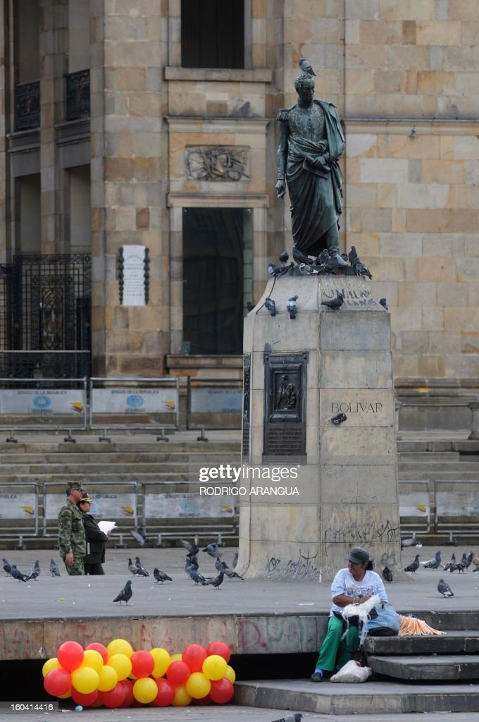 People sit beside a staute of South American independece hero Simon Bolivar in Bogota on February 9, 2010. AFP PHOTO/Rodrigo ARANGUA /