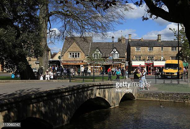 People sit beside the river as they enjoy the fine weather in the Cotswold town of BourtonontheWater on April 12 2011 in Gloucestershire England A...