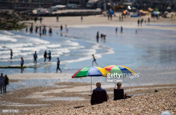 People sit beside the sea as they enjoy the fine weather on the beach in Lyme Regis on May 25 2017 in Dorset England Parts of the UK are currently...