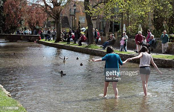 People sit besides the river as they enjoy the fine weather in the Cotswold town of BourtonontheWater on April 12 2011 in Gloucestershire England A...