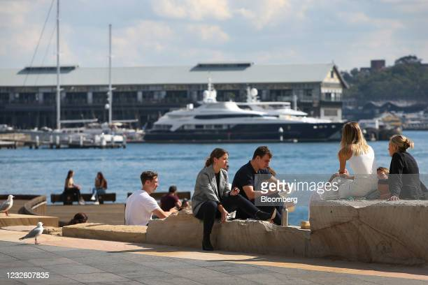 People sit by Darling Harbour in Sydney, Australia, on Friday, April 30, 2021. The government has tamed the virus by shuttering the international...
