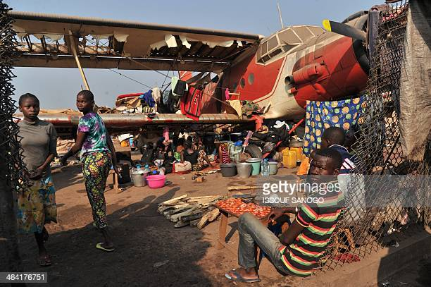 People sit by planes in the camp for displaced persons at the Mpoko airport in Bangui on January 21 2014 The European Union agreed on January 20 to...