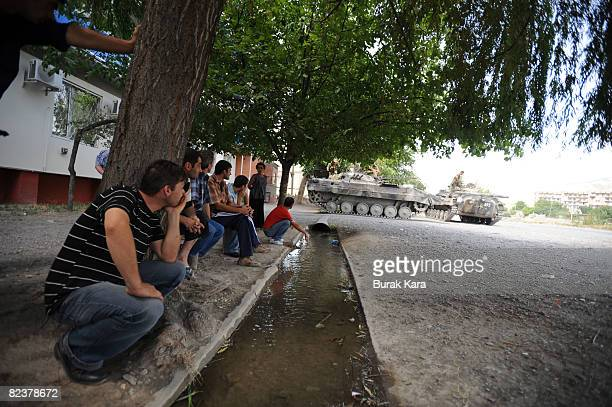 People sit by the roadside watching Russian troops take positions on August 16 2008 near the village of Igoeti on the road from Gori to Tbilisi about...