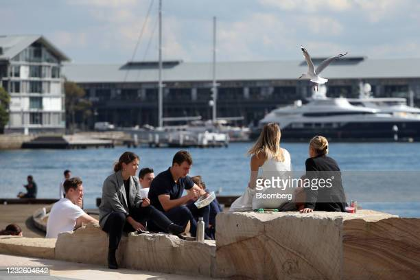 People sit by the water at Darling Harbour in Sydney, Australia, on Friday, April 30, 2021. The government has tamed the virus by shuttering the...